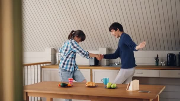 Adorable young couple playful man and woman are dancing and laughing in kitchen at home enjoying free time and good mood. Dance, music and youth concept.