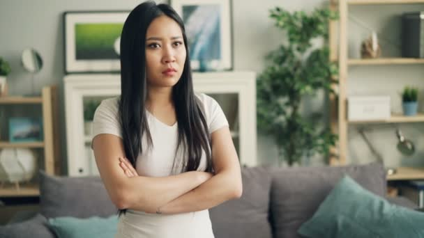 Portrait of upset Asian girl looking at camera, making sad face and expressing negative emotions standing with arms crossed at home. Woman is wearing casual clothing.