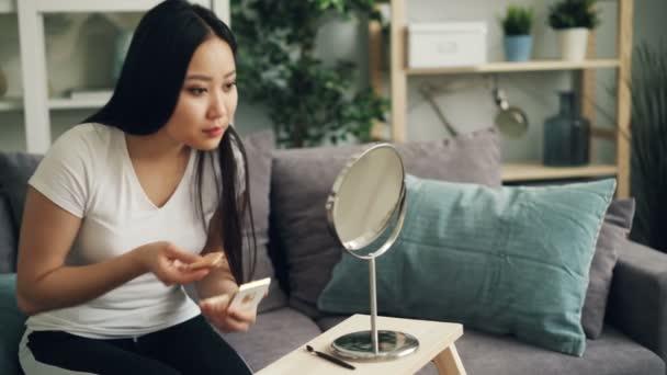 Krásná mladá dáma je dávat make-up používat pudr na obličej a pak hledá v zrcadle a hladil její vlasy těší stylový vzhled. Krásný koncept lidí a kosmetika