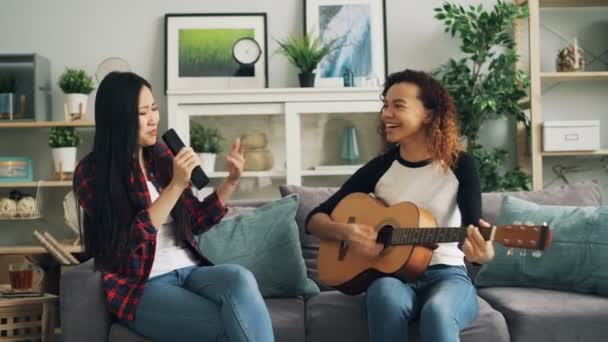 Female friends are having fun at home playing the guitar and singing in TV remote control enjoying leisure activity at home together. Music and culture concept.
