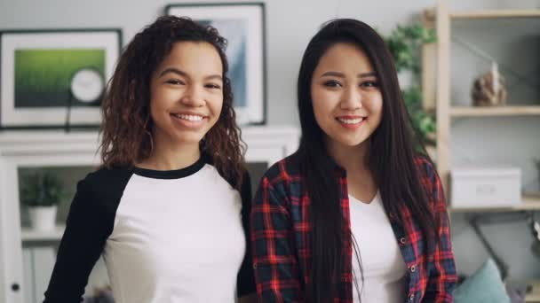 Slow motion portrait of good-looking girls mixed-race friends African American and Asian looking at camera and smiling standing inside beautiful house.