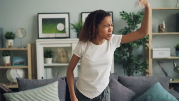 Portrait of angry African American woman yelling and gesturing expressing negative emotions standing in modern apartment. Human feelings and people concept.