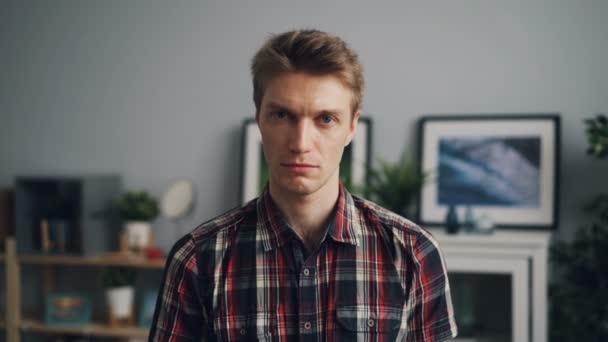 Portrét pohledný mladý muž pohledu kamery se nešťastný tvář nosí světlé kostkovanou košili postavení v moderní byt sama. Koncept mládeže a emoce.