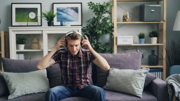 Zoom-ban a boldog srác melomaniac elhelyezés fejhallgató és hallgató-hoz zene és mosolyogva élvezi dallam és a ritmus, a kanapén ülve. Ifjúsági kultúra és életmód fogalma.