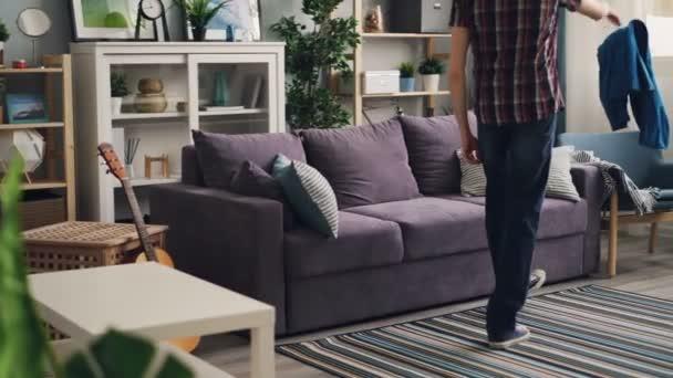 Unavený mladý muž přichází do moderního bytu házet oblečení na křeslo a pak relaxovat na gauči ležet a protažení si odpočinek po náročném dni v práci.
