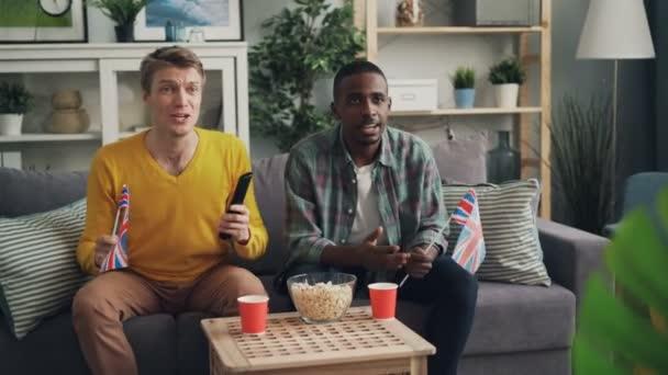 aufgeregte junge Leute unterstützen das britische Team, schauen sich Sportspiele im Fernsehen an und schwenken Flaggen großer Briten, die auf der Couch sitzen und dann High-Five machen und lachen.
