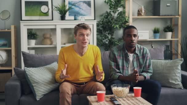 Örömteli férfi hallgatók figyeli a Tv támogatja a kedvenc csapat sport játék, akkor ünnepli győzelmét taps kezek, táncol és kacag, szórakozás.