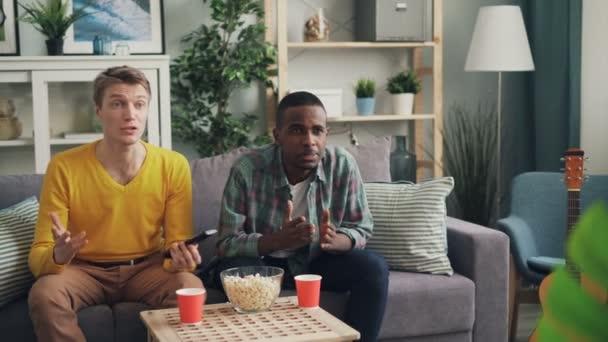 Emotionale junge Männer beobachten Spiel am Tv Fernbedienung halten dann mit dem Ausdruck negativer Emotionen Enttäuschung und Wut über Spiel und unterlegene team.