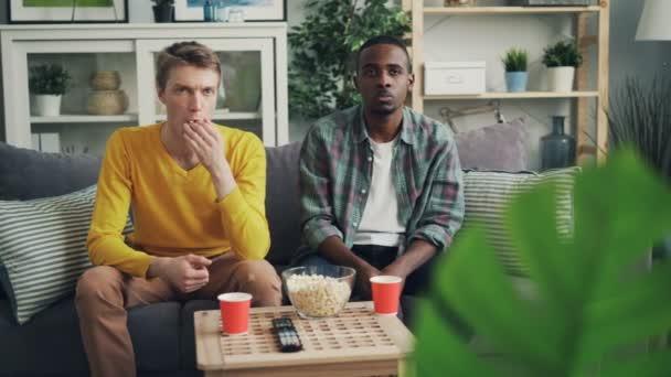 Ideges fiatal férfiak afrikai-amerikai és kaukázusi meg nézi a televíziót, érzelemmentes arcok, és eszik popcorn ül a kanapén, otthon együtt.