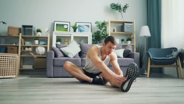 Attractive guy sportsman doing stretching exercises bending forward to one leg.