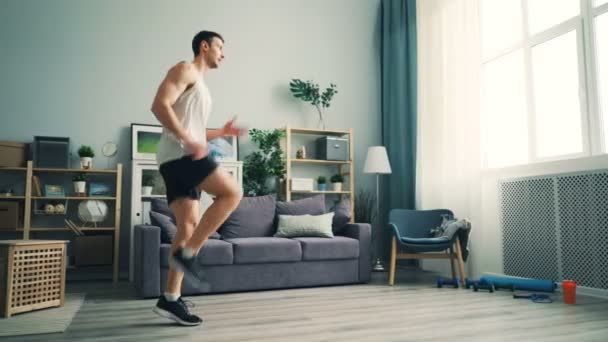 Active male sportsman is doing cardio exercises at home raising legs working out