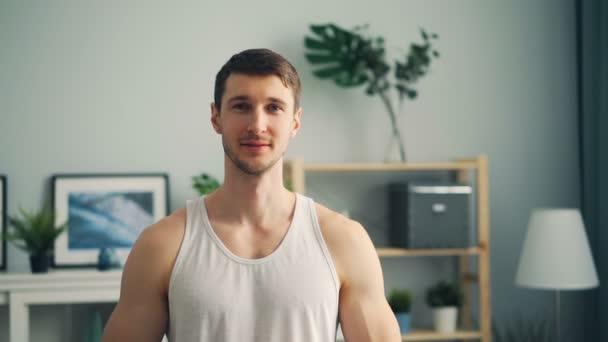 Pomalý portrét hezkého sportovec doma s úsměvem na kameře