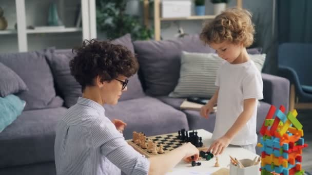 Mother and small son placing chess pieces on chessboard playing at home at table