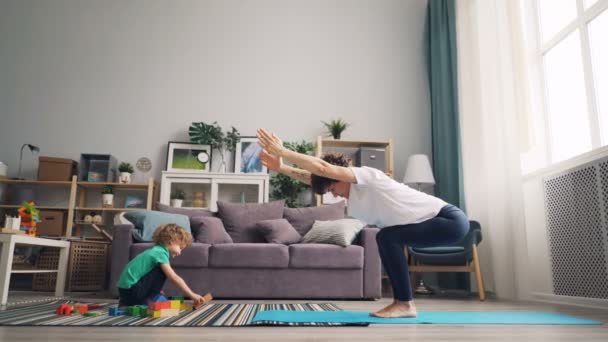 Beautiful mother doing yoga at home and watching her son playing with toys