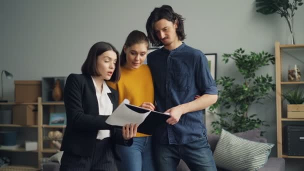Girl and guy buyers talking to housing agent reading contract in new apartment