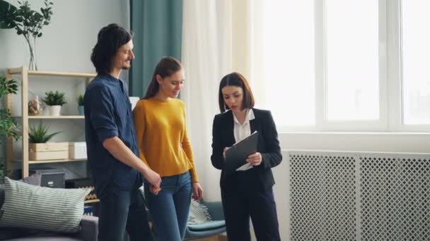 Friendly realtor talking to clients man and woman showing papers in new house