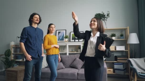 Realtor showing new house to couple talking while buyers looking around smiling
