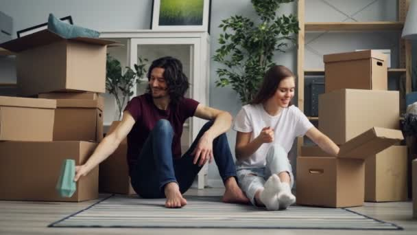 Mladá žena bere věci z krabice a mluví s přítelem během přemístění