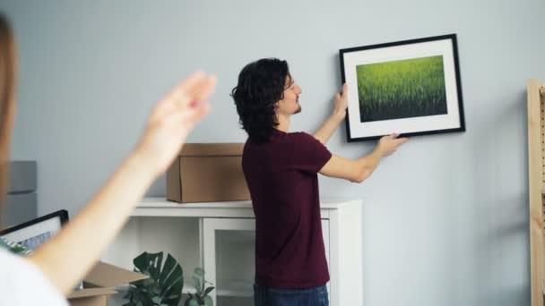 Mladý pár si vybírá místo pro obrázek na zdi v novém domě po přemístění