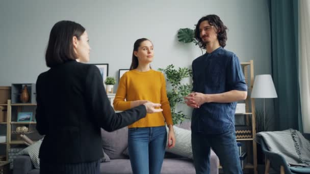 Girl and guy discussing new apartment with real estate agent talking indoors