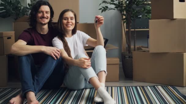 Portrait of couple holding keys to new flat sitting on floor with boxes around