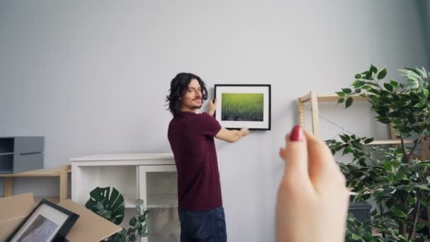 Young man choosing place for picture while girlfriend helping him gesturing
