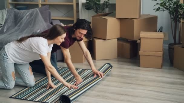 Happy girl and guy unrolling carpet at home and talking then lying relaxing