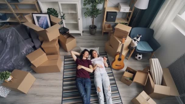 Girl and guy chatting and gesturing lying on floor after moving to new apartment