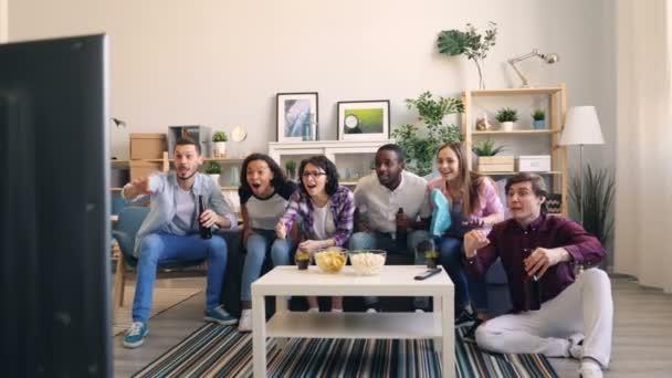 Sportliche Jugend schaut Sportspiel im Fernsehen lachend High-Five-Bier haltend