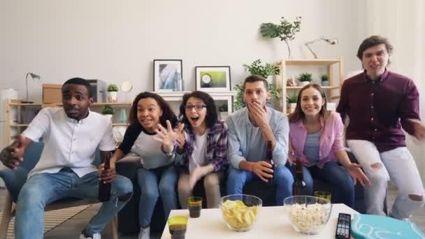 Mädchen und Jungen sind glücklich, nachdem sie zu Hause gemeinsam Sportspiele im Fernsehen gesehen haben