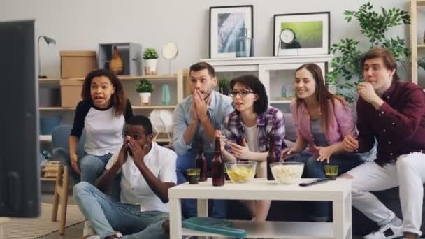 Multiracial Gruppe von jungen Menschen jubeln Sportmannschaft fernsehen zu Hause