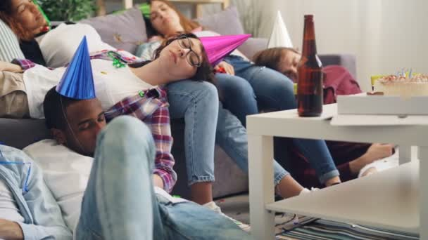 Exhausted girls and guys sleeping on floor and sofa after party in apartment