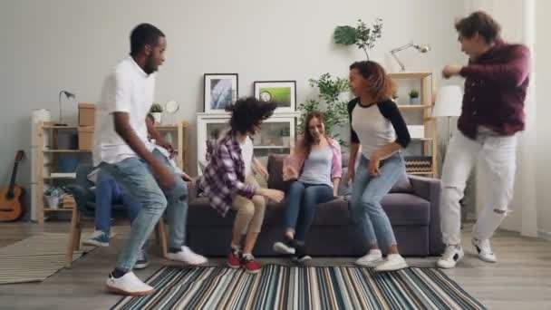 Slow motion portrait of girls and guys running to sofa sitting looking at camera