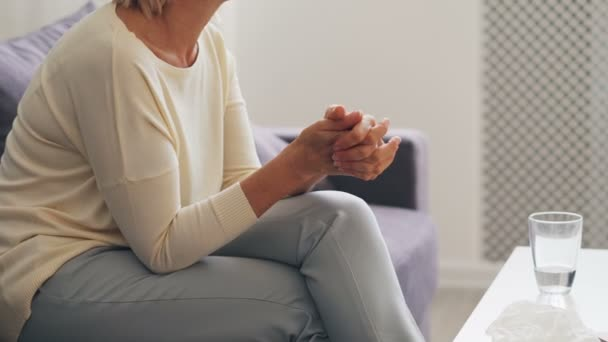 Elderly woman talking and gesturing during therapy session with psychologist