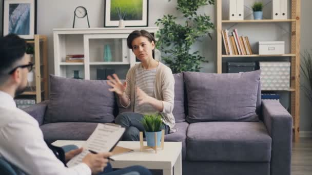 Cheerful woman speaking with psychological counsellor sitting on sofa in office