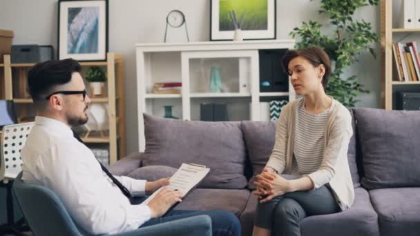 Therapist talking to female patient in office making notes asking questions