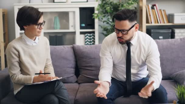 Helpful therapist comforting angry businessman during consultation in office