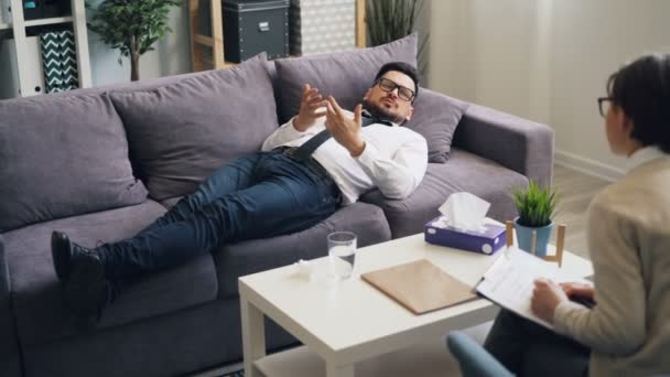 Unhappy young man speaking lying on sofa in psychologists office in clinic