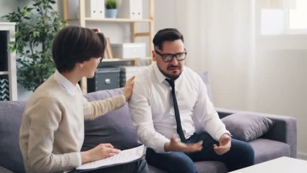 Caring psychologist comforting mad guy angry businessman during consultation