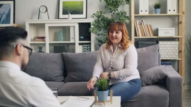 Übergewichtige Frau spricht mit Therapeut und lächelt während Konsultation in Klinik