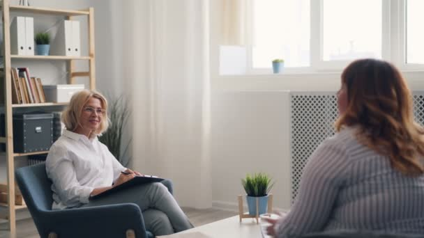 Successful psychologist talking to overweight young woman during therapy session
