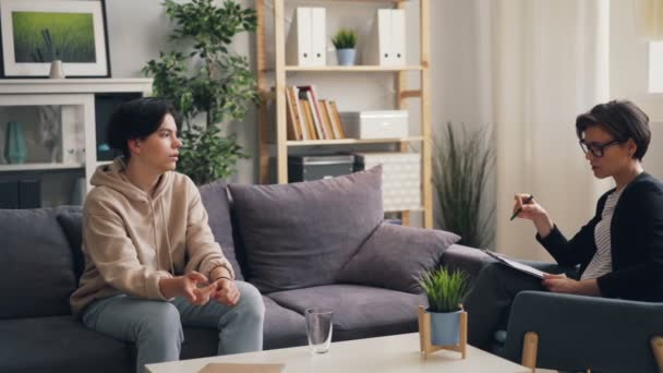Friendly psychologist young woman counseling unhappy teenager in office