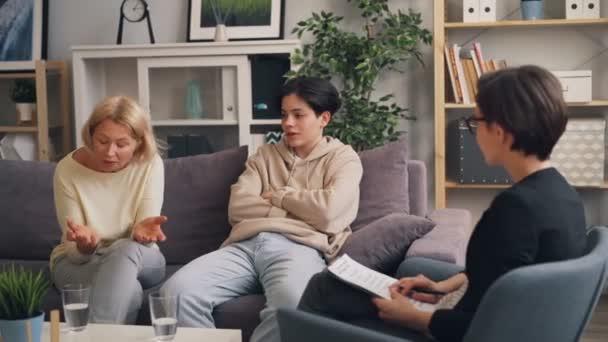 Nešťastná rodinná matka a syn, kteří hovoří s psychoterapeutem na moderní klinice
