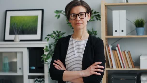 Pomalý pohyb, portrét ženy, která se dívala na fotoaparát s úsměvem v kanceláři