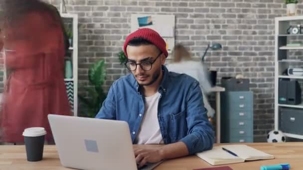 Zoom out time-lapse of male employee working with laptop busy with project