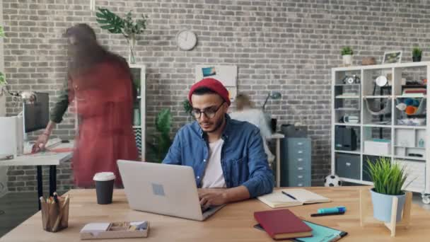 Time-lapse of young man working with laptop in office while colleagues moving