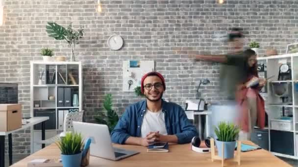 Zoom in time-lapse of happy business owner looking at camera smiling in office