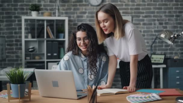 Young ladies colleagues talking looking at laptop screen in office room at desk