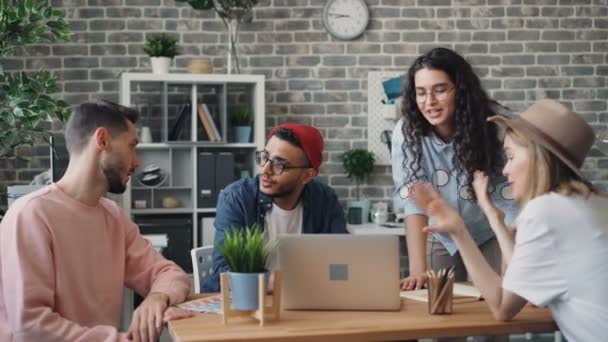 Girls and guys coworkers discussing project pointing at laptop screen in office