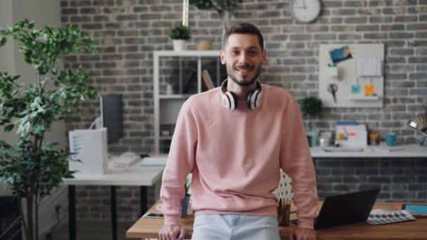 Portrét hezkého mladého kancelářského pracovníka, který se dívá na kameru a usmívá se